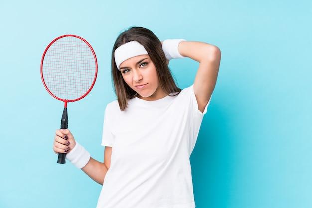 Молодая caucasic женщина играет в бадминтон, касаясь затылок, думая и делая выбор