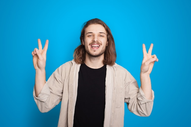 こんにちはとピースのサインを身振りで示す長い髪のコーカシーナの男は青い背景に笑っています