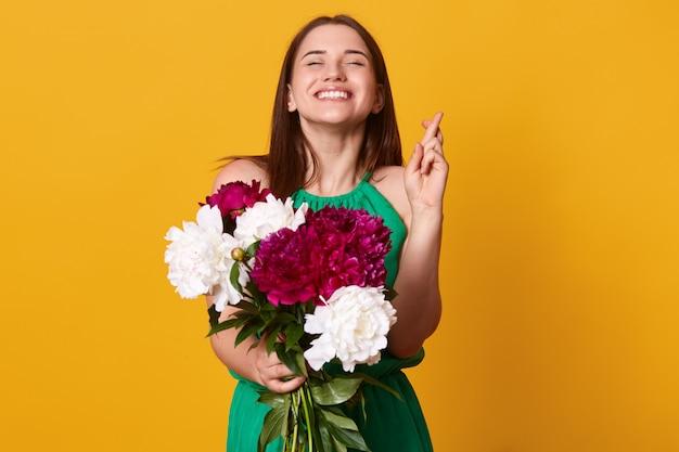 Кавказская женщина поднимает скрещенные пальцы, молится о удаче, имеет радостное и счастливое выражение лица, носит зеленый сарафан, держит белые и бордовые пионы, верит в удачу.