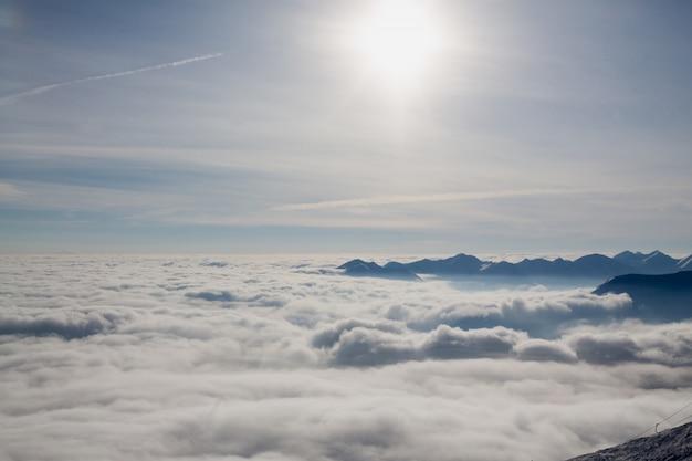 コーカサス山脈の頂上は日の出後の太陽に照らされた雲の上のピークです。ジョージア州カズベク山からの素晴らしい眺め。旅行の動機のコンセプト。