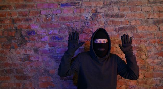 밤에 벽돌 벽 근처에 서 있는 도둑을 잡았다