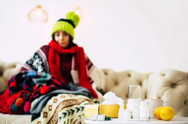 Caught cold. cute young ill woman is feeling cold and sick sitting on a couch and being warmly dressed in a sweater, scarf and green knitted hat.