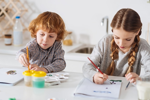 Caught in imagination. charming lovely adorable siblings drawing pictures using watercolors while sitting at the white table together