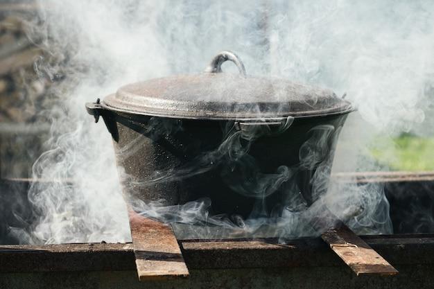 연기에 덮인 모닥불 위의 가마솥. 금속 냄비에 불에 야외 음식을 요리.