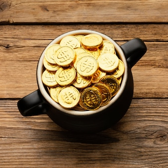 Cauldron with gold coins on wooden background