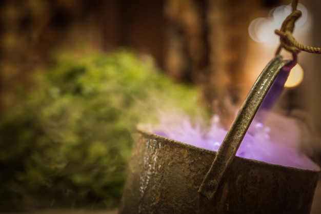 Cauldron with purple magic boiling potion or witching toxic poison soup.
