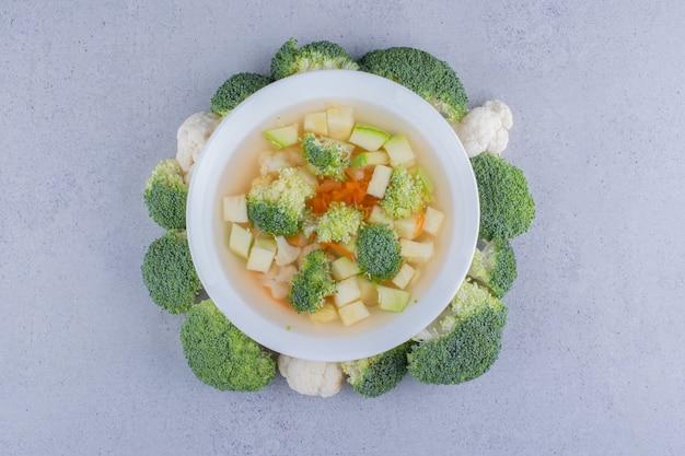 Суп из цветной капусты и брокколи в миске, окруженной брокколи на мраморном фоне.