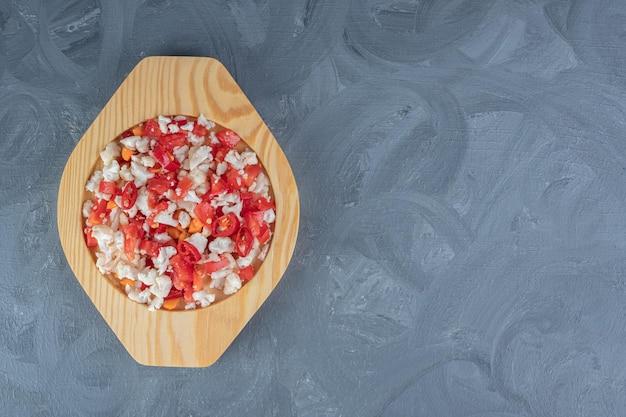 大理石の背景にニンジンを混ぜた木製の大皿にカリフラワーとピーマンのサラダ。