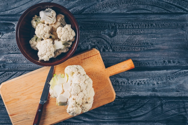 Cauliflower in a bowl and cutting board with knife top view on a dark wooden background