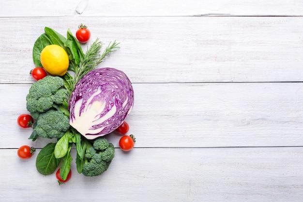 Цветная капуста, брокколи, голубая капуста, лимон и помидоры черри на белом фоне деревянные. фоновое меню еды