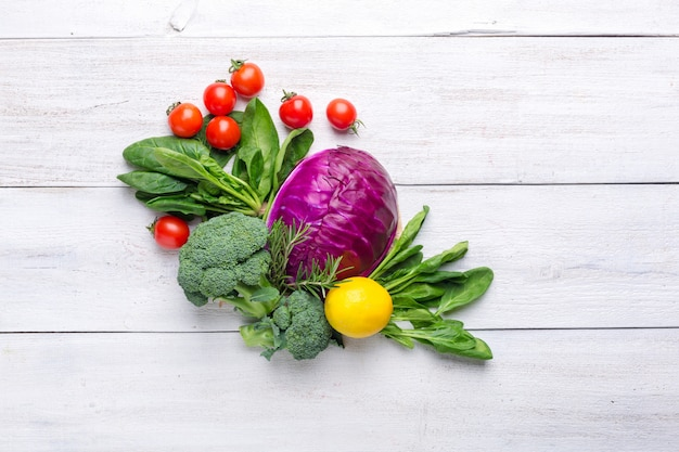 Cauliflower, broccoli, blue cabbage, lemon and cherry tomatoes on a white wooden background. background menu food