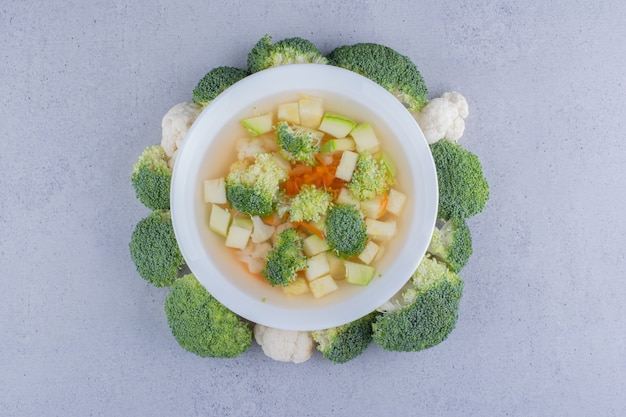 Cauliflower and broccoli soup in a bowl ringed with broccoli on marble background.