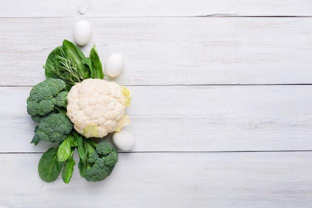 Цветная капуста, брокколи, шпинат и куриные яйца на белом фоне деревянные. фоновое меню еды