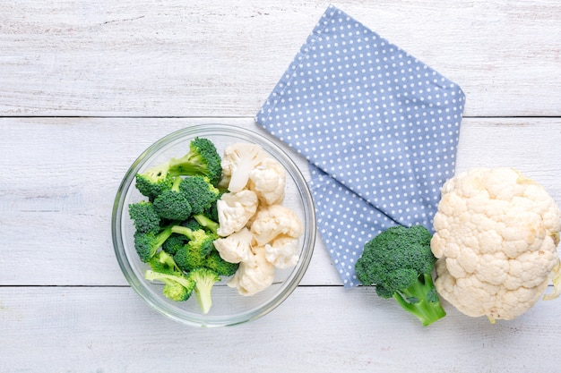 Cauliflower and broccoli in a transparent bowl on a white wooden background. background menu food