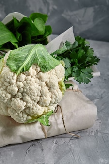 Цветная капуста, свежие овощи на сером фоне с пространством для текста. натуральное питание, правильное питание.