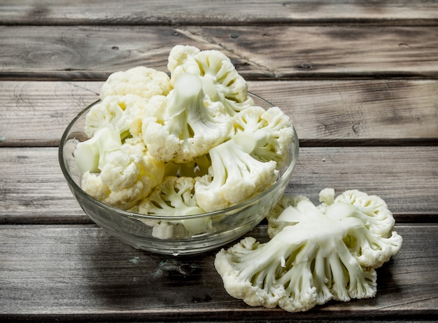 Cauliflower in a glass bowl. on a wooden background.