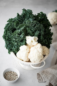 Cauliflower and kale in a white colander on a white table