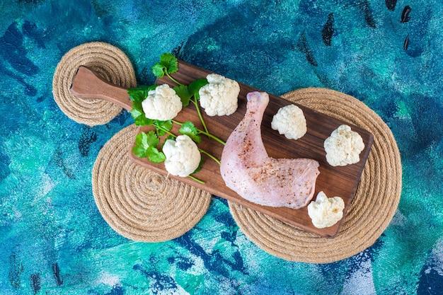 Cavolfiore e coscia di pollo marinata su un tagliere su un sottopentola