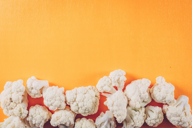 Cauliflower on a orange background. top view. space for text