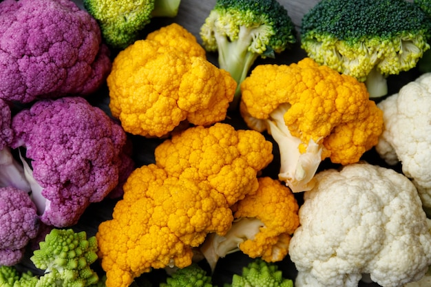 Cauliflower and romanesco broccoli on wooden background. healthy food concept.