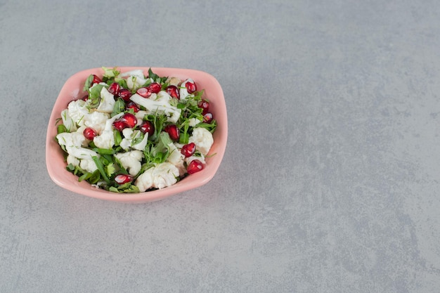 석류 씨앗과 허브와 함께 접시에 콜리 플라워 샐러드.
