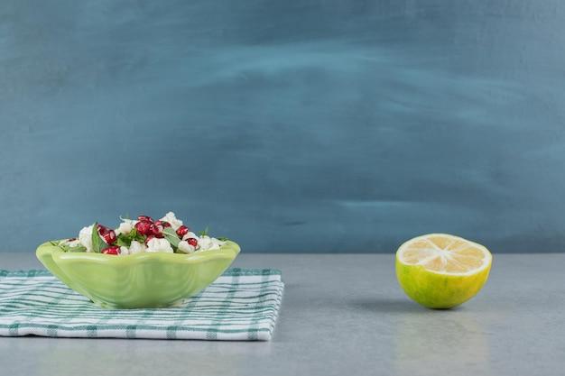 Insalata di cavolfiore nel piatto con semi di melograno ed erbe aromatiche.