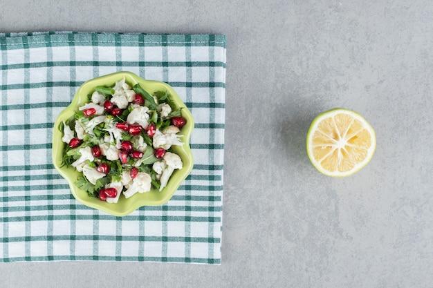 Салат из цветной капусты с зеленью и зернами граната.