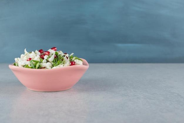 접시에 붉은 석류 씨앗과 콜리 플라워 샐러드.
