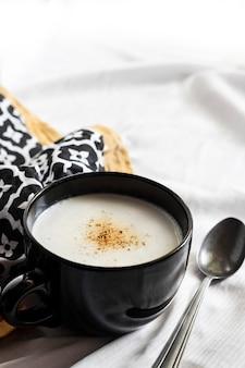 Cauliflower soup creme du barry in black bowl on white background