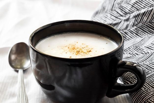 Суп из цветной капусты (creme du barry) в черной миске на белой поверхности с черно-белой тканью