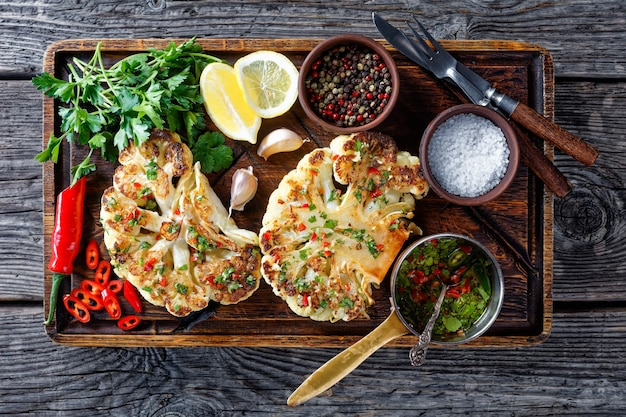 Cauliflower steaks on a wooden cutting board sprinkled with the salsa of chili, red vinegar, garlic, and cilantro
