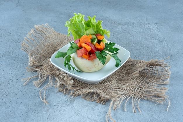 Цветная капуста под листьями петрушки, салатом и нарезанными овощами на блюде на мраморном столе.