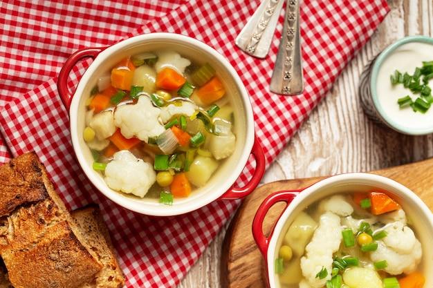 Суп из цветной капусты в миску, хлеб, сливки на деревянный стол