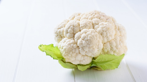 Cauliflower with leaves on a white wooden table.