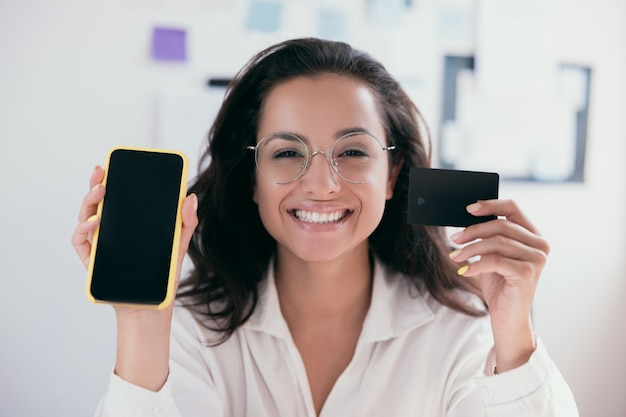Causasian cheerful young woman with brown hair holding a card and smartphone, smiling and looking at camera