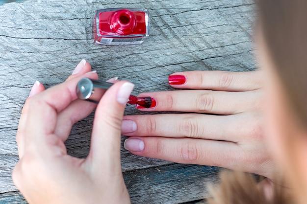爪に赤いニスを塗る、マニキュア_