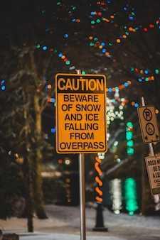 Caution beware of snow and ice falling from overpass sign