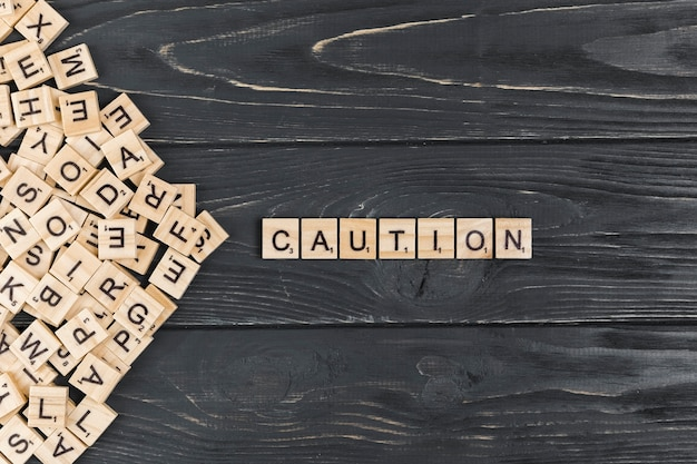 Caution word on wooden background