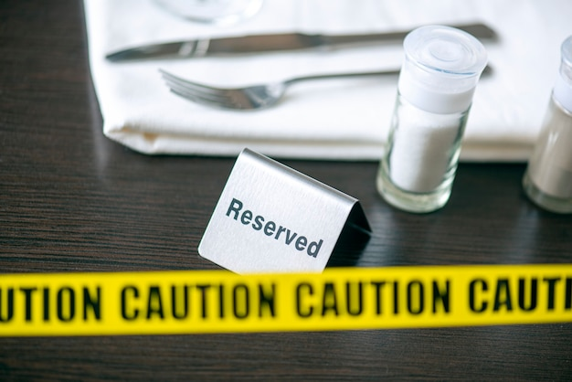 주의-카페 또는 레스토랑의 테이블 위에 노란색 테이프 및 기호 예약. 사회적 거리두기