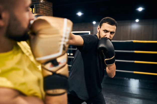 Cautious boxer in black sportswear hitting his sparring partner with a straight blow to the head