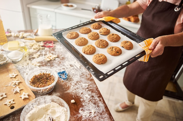 テーブルにホットクッキーとトレイを運ぶ慎重な女性