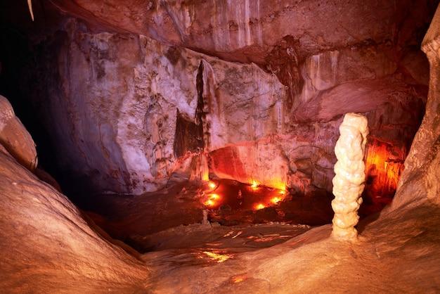 Темный интерьер пещеры со светлыми сталактитами и сталагмитами