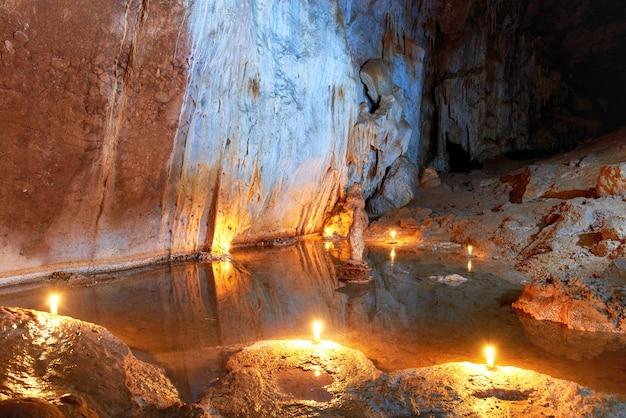 Темный интерьер пещеры с подземным озером, светом, сталактитами и сталагмитами