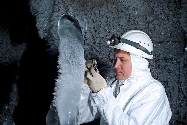 동굴 탐험가는 어두운 암석 벽의 배경에 있는 얼음 석순을 조사합니다