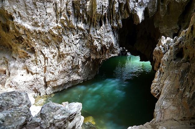 川の水で満たされた岩の洞窟。メインセールの石の表面にまぶしさ。洞窟の壁に液体の反射