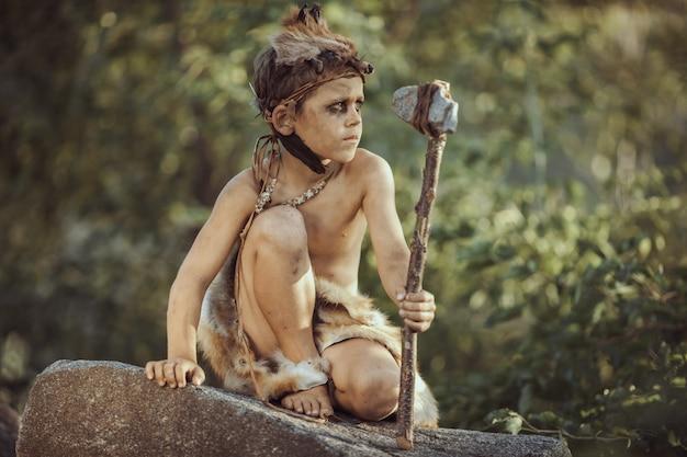 Пещерный человек, мужественный мальчик с примитивным оружием охоты на открытом воздухе.
