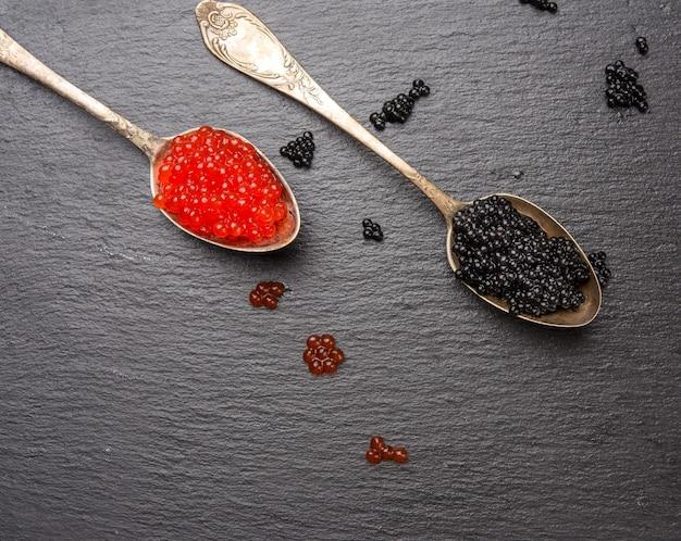 Икра веслоноса и икра красной кеты в ложке, черный фон, вид сверху
