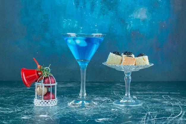 Spuntini al caviale su un piedistallo di vetro accanto a un bicchiere di cocktail e ornamenti natalizi su blu.