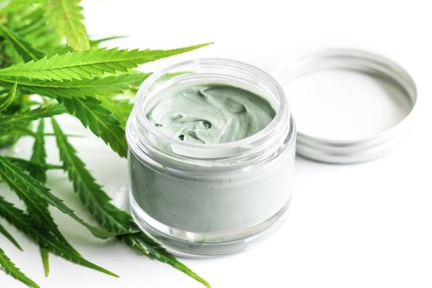 Cbd cosmetics. green cannabis plant and jar with a moisturizing rejuvenation cream.
