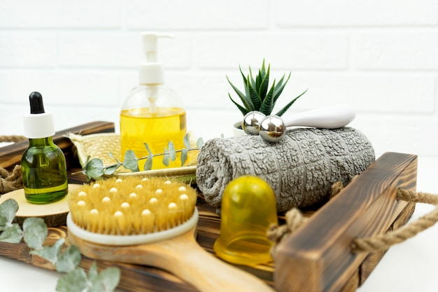 A cbd green oil, face roller, a brush for dry massage stand on a wooden tray in a bathroom